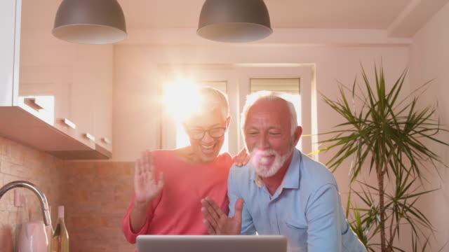 vidéos et rushes de couple de personnes âgées utilisant la technologie pour rester en contact avec la famille - petit enfant