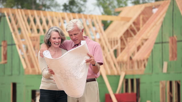 Senior couple viewing blueprints in front of house under construction
