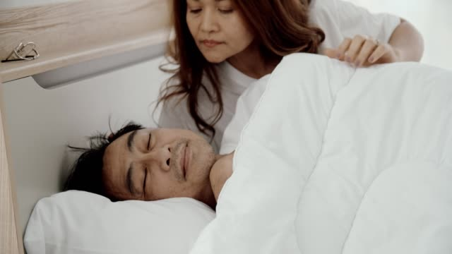 vídeos de stock e filmes b-roll de senior couple waking up and kissing in bedroom in morning - camisola sem manga