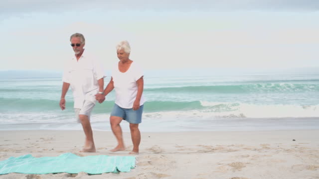 senior couple walk and sit on a sarong on a white beach - sarong stock videos & royalty-free footage