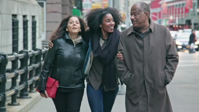 Senior Couple Walk with their Adult Daughter