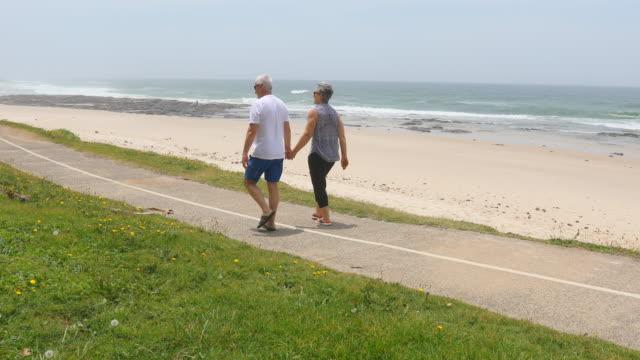 senior couple walking along a beachside path - leisure activity stock videos & royalty-free footage