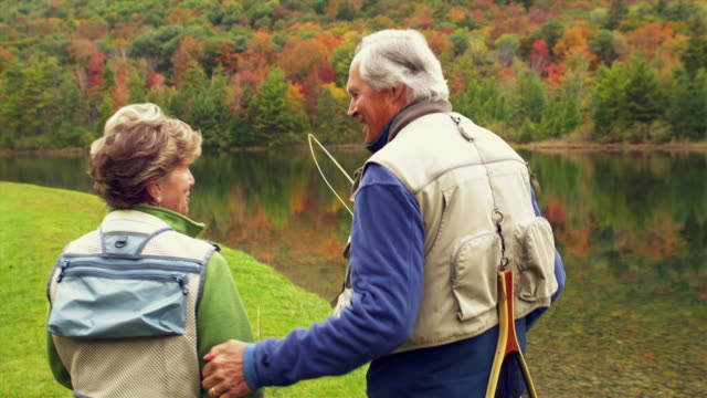 MS SHAKY SWISH PAN Senior couple walking along lake shore carrying fishing rods, Manchester, Vermont, USA