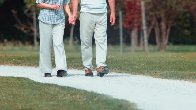 TU Casal idoso a andar e segurando as mãos