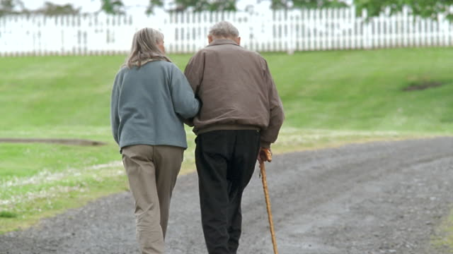 ws td senior couple walking arm in arm along dirt road / washington state, usa - älteres paar stock-videos und b-roll-filmmaterial