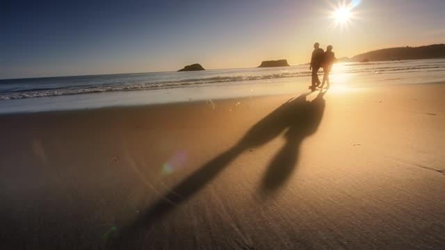 Senior couple walking beach at sunset, Oregon