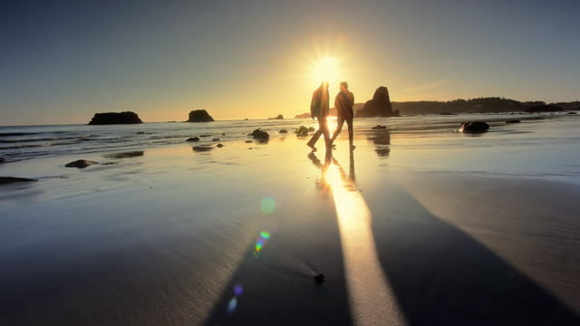 senior couple walking beach at sunset, oregon - controluce video stock e b–roll