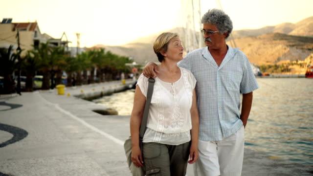 vídeos de stock, filmes e b-roll de sênior casal andando pelo mar - jovem de espírito