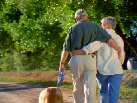 Senior couple walking dog on country road away from camera