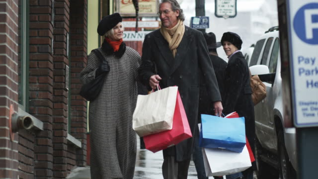 senior couple walking down a snowy street with shopping bags