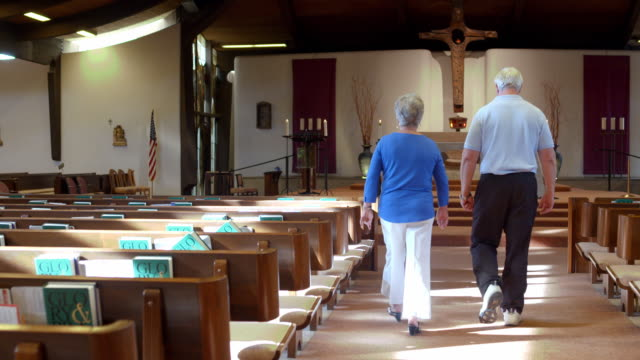 vídeos de stock, filmes e b-roll de ts senior couple walking down center aisle alongside empty pews towards altar and genuflect before sitting down in pew - cruz objeto religioso