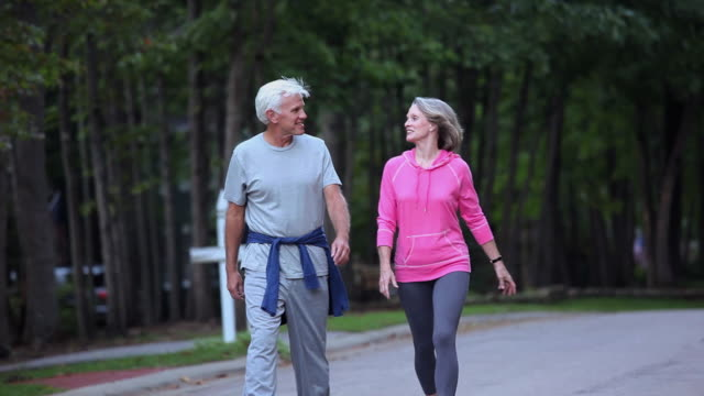 ms pan zo pov senior couple walking for exercise in suburban neighborhood / richmond, virginia, united sates - walking exercise stock videos and b-roll footage