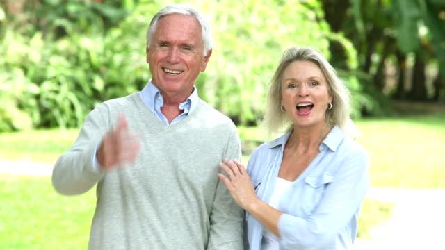 Senior couple walking, holding hands, talking