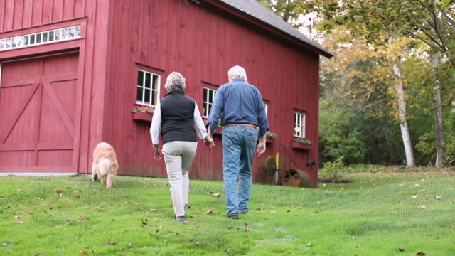 Senior couple walking in front of barn