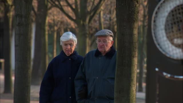 vidéos et rushes de ms pan senior couple walking in luxembourg garden / paris, france - manteau et blouson d'hiver
