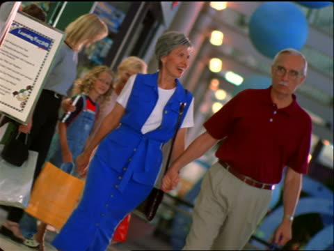 vídeos y material grabado en eventos de stock de canted senior couple walking in mall followed by girl + two women with shopping bags - 1990