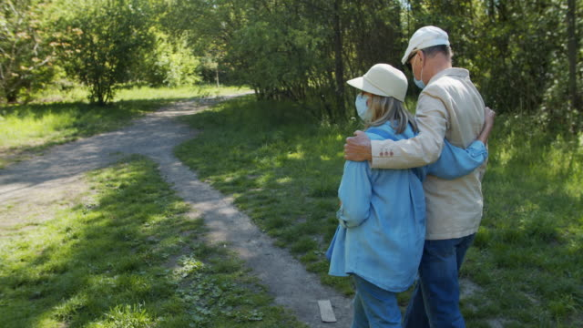 senior couple walking in park during covid-19 pandemic - selective focus stock videos & royalty-free footage