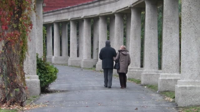 senior couple walking in the archway - architectural column stock videos & royalty-free footage