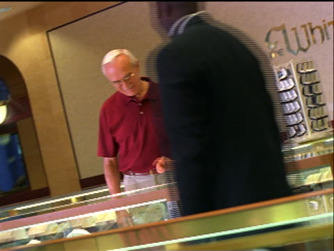 CANTED PAN senior couple walking into jewelry store + being helped by Black salesman