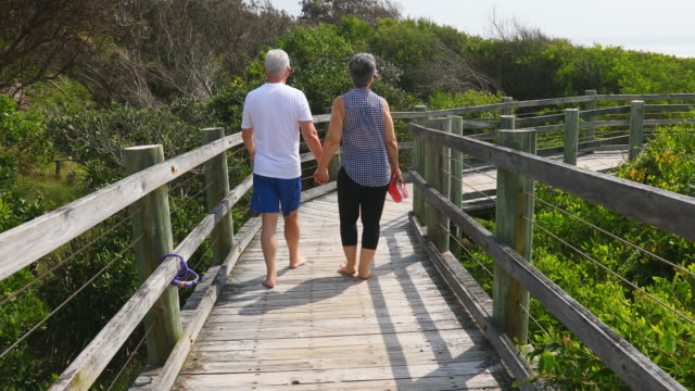 senior couple walking on a boardwalk at the beach - mature couple stock videos & royalty-free footage