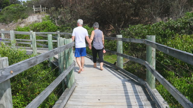 senior couple walking on a boardwalk at the beach - leisure activity stock videos & royalty-free footage