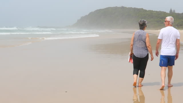 senior couple walking on a pristine beach - retirement stock videos and b-roll footage