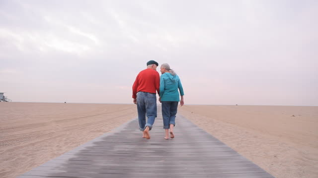 ws td senior couple walking on beach boardwalk / los angeles, california, usa - schwenk nach unten stock-videos und b-roll-filmmaterial