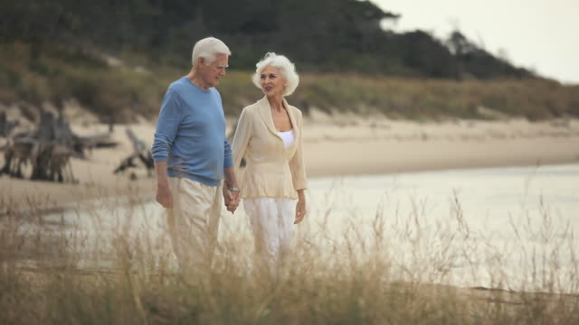 MS PAN Senior couple walking on beach, Eastville, Virginia, USA