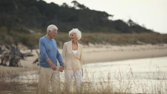 ms pan senior couple walking on beach, eastville, virginia, usa - senior couple stock videos & royalty-free footage