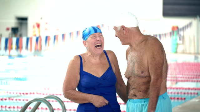 senior couple walking on indoor pool deck, holding hands - candid stock videos & royalty-free footage