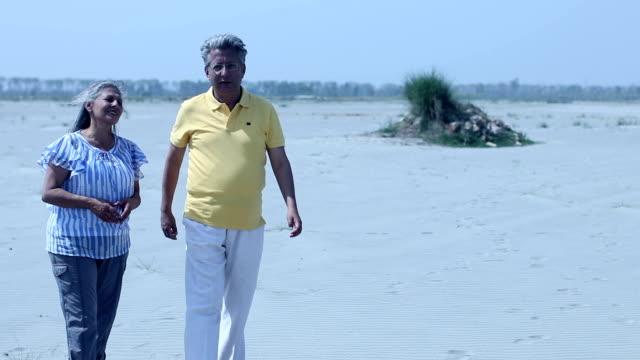 senior couple walking on sand, haryana, india - gå tillsammans bildbanksvideor och videomaterial från bakom kulisserna