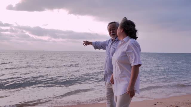 在海灘上散步的老年夫婦, 在陽光明媚的日子裡, 高級夫婦在海邊放鬆。高級假期, 假期 - 晴朗 個影片檔及 b 捲影像