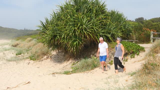 senior couple walking on the beach through sand dunes - leisure activity stock videos & royalty-free footage