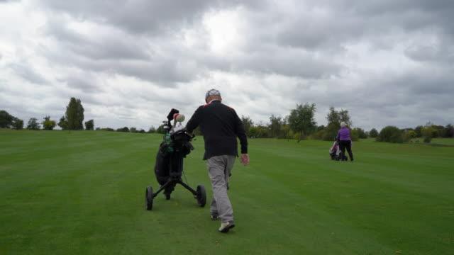 vídeos de stock, filmes e b-roll de a senior couple walking on the fairway. - bolsa de golfe