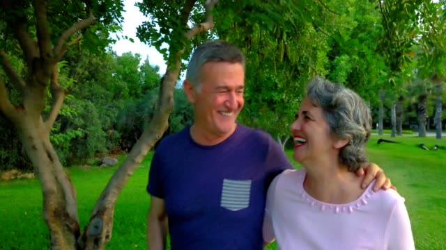 senior couple walking on the park, having fun, laughing and talking. - 50 54 years stock videos & royalty-free footage