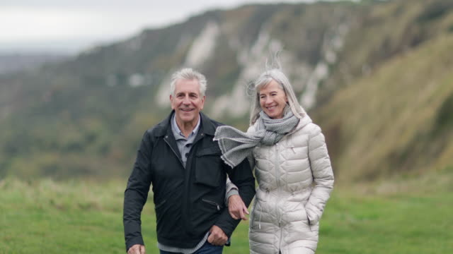 senior couple walking outdoors - pensionierung stock-videos und b-roll-filmmaterial