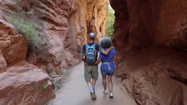 4k uhd: senior couple walking through canyon - retirement stock videos & royalty-free footage