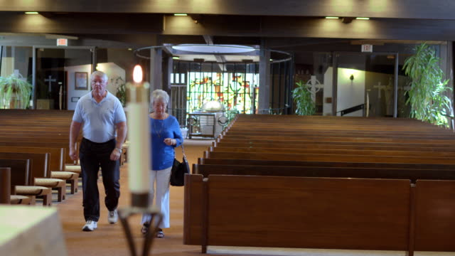 LS TS senior couple walking towards camera down main aisle of empty catholic church and genuflecting just before sitting down in pew
