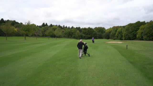 vídeos de stock, filmes e b-roll de a senior couple walking up the golf course with their buggies. - bolsa de golfe