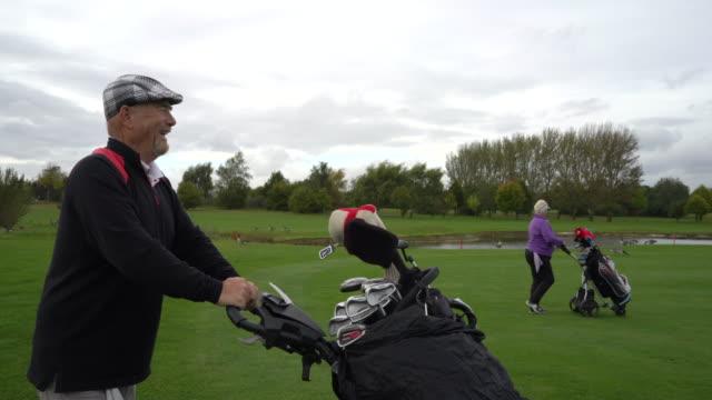 vídeos de stock, filmes e b-roll de a senior couple walking with their golf carts to the next hole. - bolsa de golfe