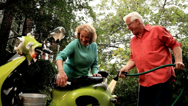 Senior Couple Washing Green Scooter