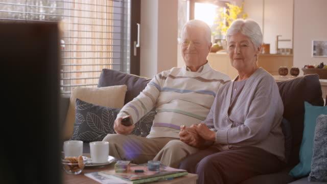 stockvideo's en b-roll-footage met senior paar kijken naar een leuke tv-show bij u thuis - television show