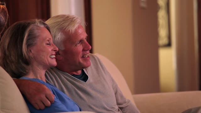 MS Senior couple watching television on couch in home living room / Richmond, Virginia, United Sates