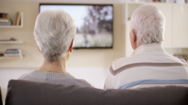 ds senior couple watching television, talking and laughing - watching tv stock videos & royalty-free footage