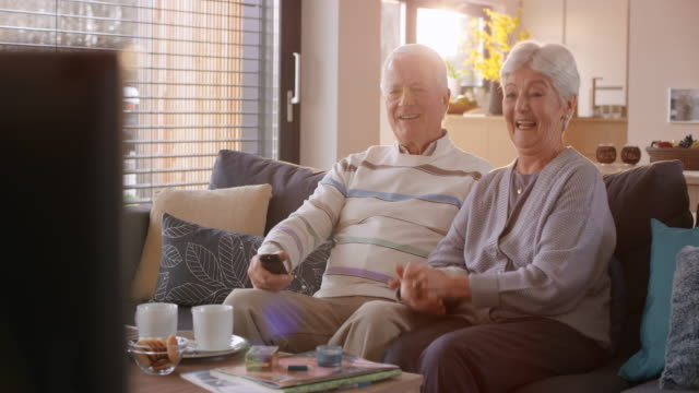 senior couple watching tv, singing and laughing - active seniors stock videos & royalty-free footage
