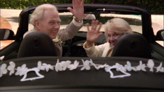 SLO MO MS Senior couple waving and sitting in convertible decorated with wedding bell streamers / Los Angeles, California, USA