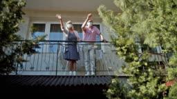 Senior couple waving from balcony during COVID-19 quarantine