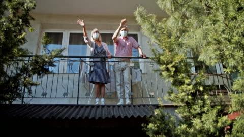 stockvideo's en b-roll-footage met hoger paar dat van balkon tijdens covid-19 quarantaine golft - waving