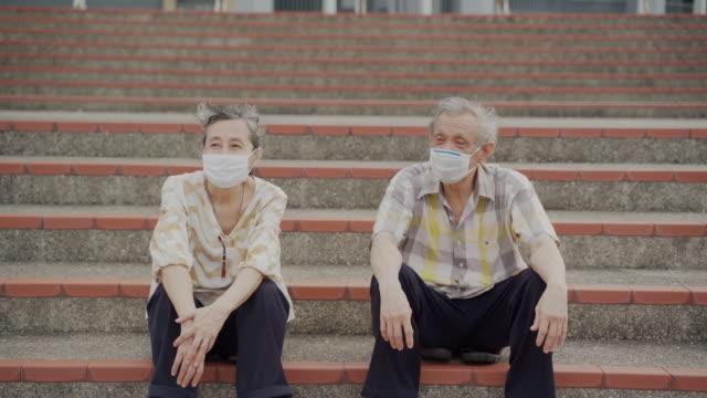 シニアカップルは、自宅の外に座って話している保護フェイスマスクを着用 - 柔軟性点の映像素材/bロール