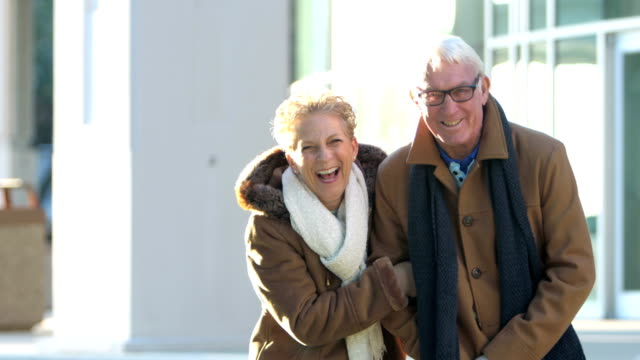 senior couple wearing coats standing outside building - 60 69 years stock videos & royalty-free footage
